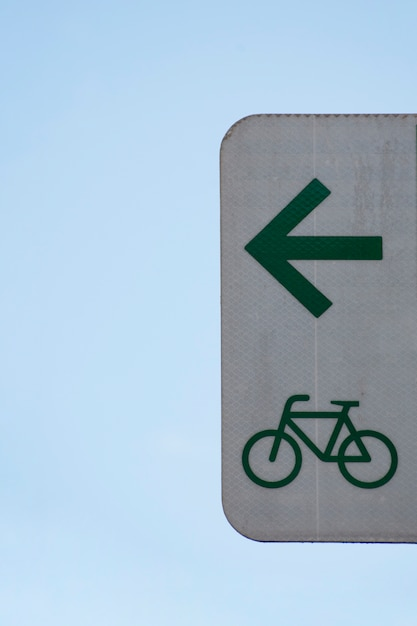 Minimalist arrow sign for bicycles and sky Free Photo