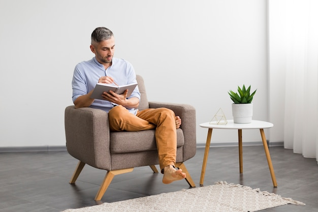 Minimalist home decor and man sitting on a chair with his agenda Free Photo