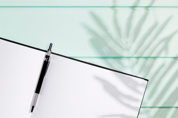 Minimalist notebook with pen and leaves shadow Free Photo