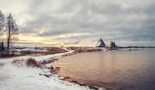 러시아 마을 Rabocheostrovsk의 해안에 정통 집이있는 미니멀리스트 눈 덮인 겨울 풍경. 프리미엄 사진