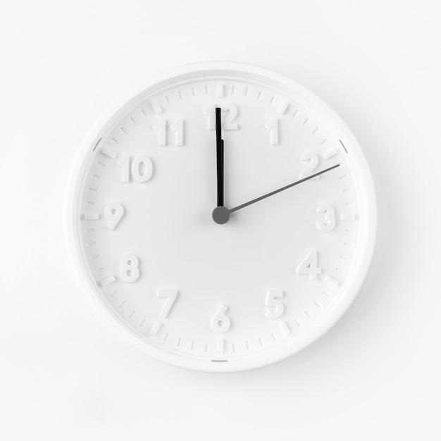 Минималистские белые часы, показывающие полночь Premium Фотографии
