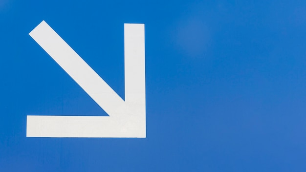 Minimalist white downstairs arrow on blue background Free Photo