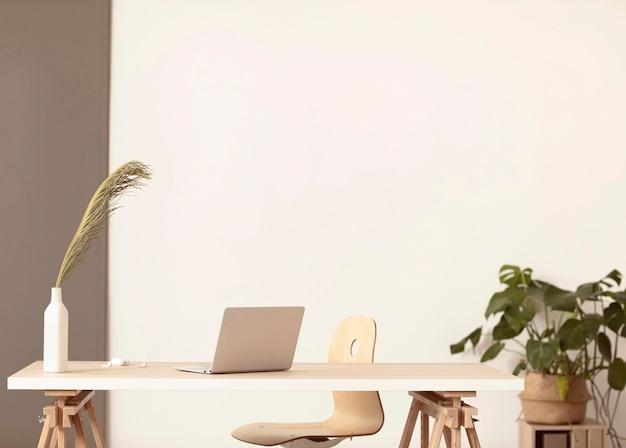 ノートパソコンと植物のあるミニマリストの職場 Premium写真