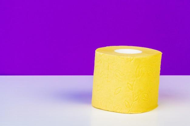Minimalistic composition of bright yellow toilet paper rolls on purple Premium Photo