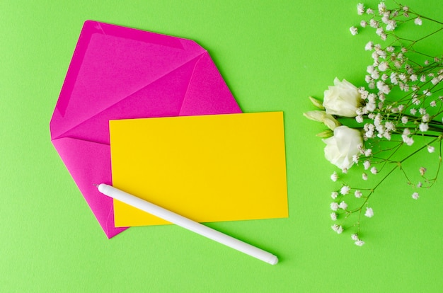 Minimalistic composition with a pink envelope, yellow blank card, pen and flowers. flay lay, mockup concept. Premium Photo