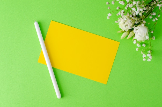 Minimalistic composition with an yellow blank card, pen and flowers on green background. flay lay, mockup concept. Premium Photo
