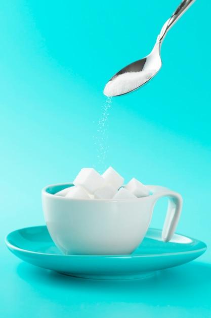 砂糖の立方体とスプーンでミニマルなカップ 無料写真