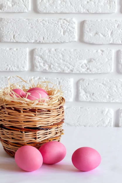 Minimalistic easter composition with wicker basket and pink colored eggs on white background. copy space Premium Photo