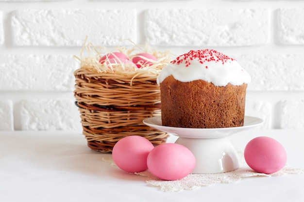 Minimalistic easter composition with wicker basket with pink colored eggs and easter cake on white background Premium Photo