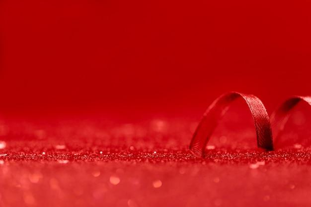 Minimalistic red ribbon decor on red shiny beautiful background Premium Photo