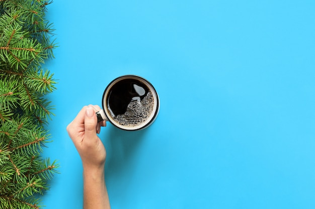 Minimalistic style woman hand holding a mug of coffee on blue Premium Photo