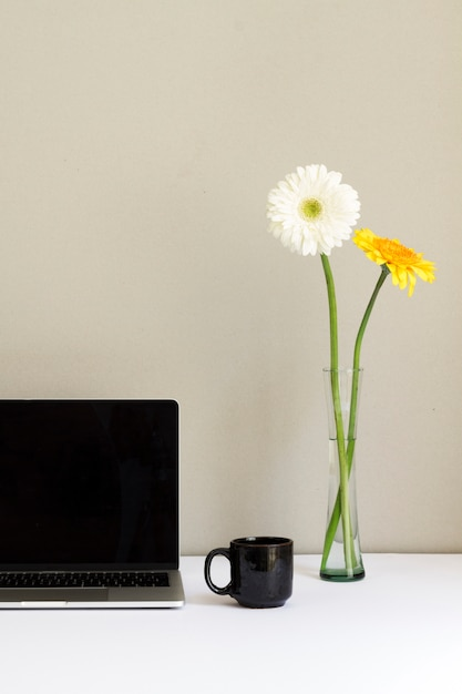 Minimalistic workplace with laptop and flowers in glass vase on desk Free Photo