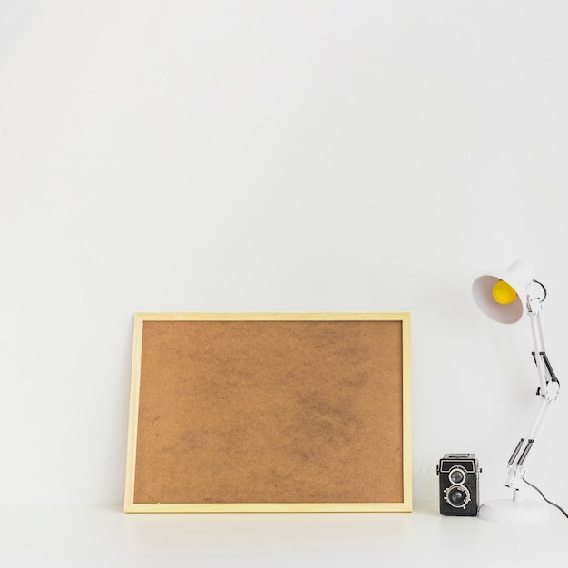 Minimalisticworkspace with cork board and old camera Free Photo