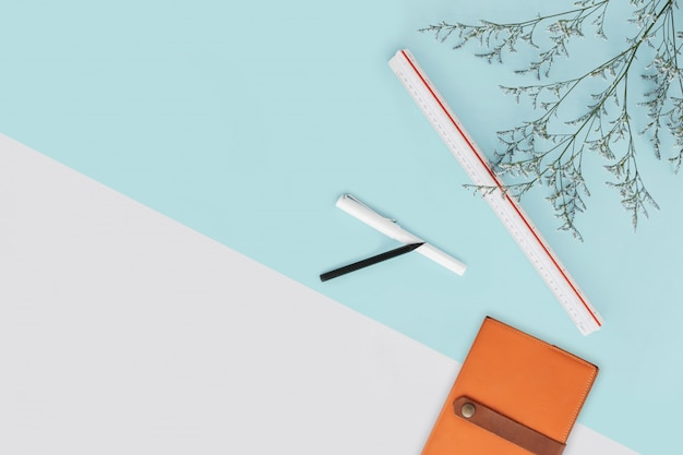 Mint green and white color background with flower branches and scale ruler, pencil, pen and notebook the right side. architect and designer background Premium Photo