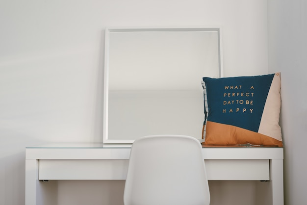 Mirror and a cushion on a white table with a chair in front Free Photo
