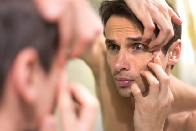 Mirror portrait of man popping a pimple Free Photo