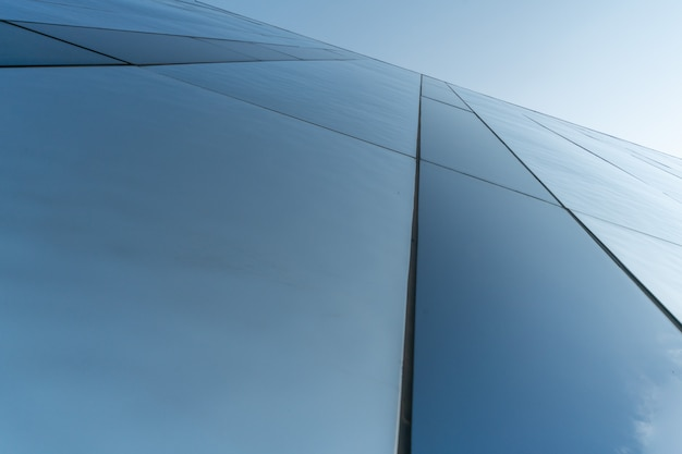 Mirror wall design of shopping center, copy space. bottom view to modern texture of exterior decoration. contemporary pattern of buildings. looking up. Premium Photo