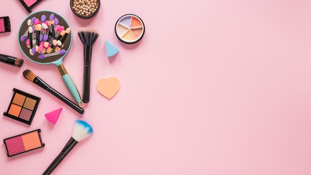 Mirror with eye shadows and powder brushes on pink table Free Photo