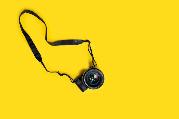 Mirrorless black camera on yellow background, summer memmories photograher Premium Photo