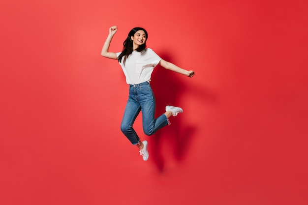 Mischievous woman in white t-shirt and jeans jumping on red wall Free Photo