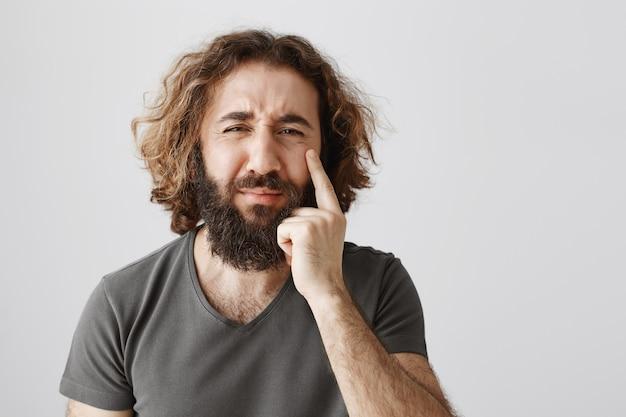 Miserabile uomo barbuto del medio oriente sconvolto che piange, mostrando lacrima Foto Gratuite
