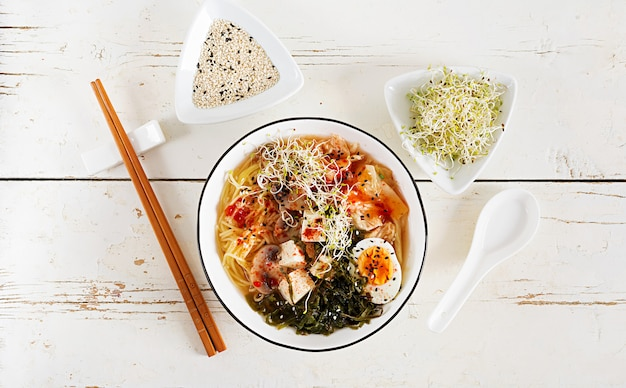 흰색 나무 테이블에 그릇에 양배추 김치, 해초, 계란, 버섯, 치즈 두부 된장국 수 프리미엄 사진