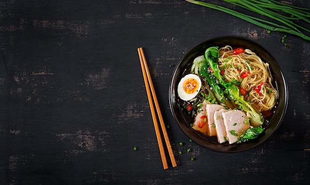 어두운 테이블에 그릇에 계란, 돼지 고기, 박 최 양배추와 함께 된장 국수 프리미엄 사진