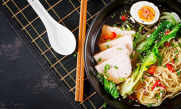 Miso noodles with egg, pork and pak choi cabbage in bowl on dark table Premium Photo