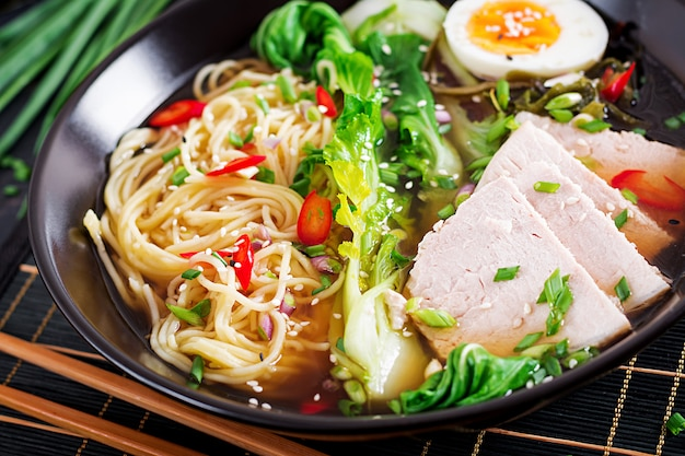Miso ramen asian noodles with egg, pork and pak choi cabbage in bowl on dark surface. Free Photo