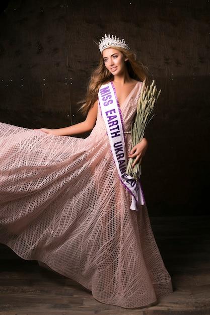 Miss earth donna che indossa la corona, il nastro e le spighette di grano. concorso di moda, bellissima modella in posa Foto Gratuite