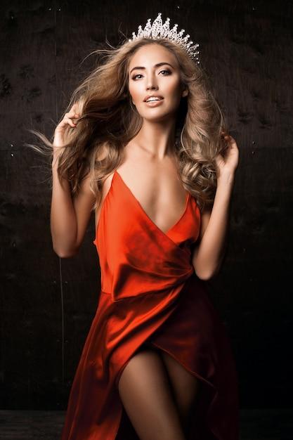 長いシルクの赤いドレスと王冠を身に着けているミスユニバース。ナチュラルメイク、巻き毛のヘアスタイル 無料写真
