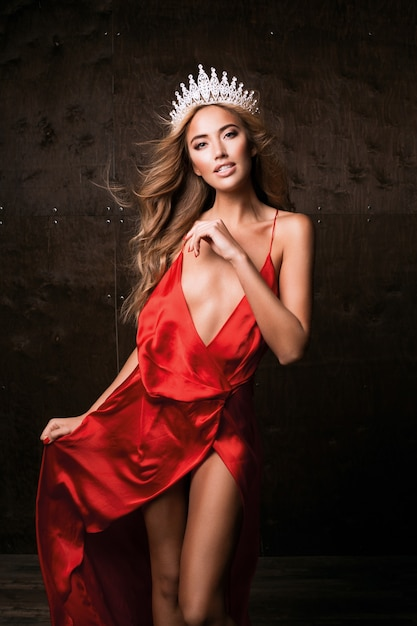 Miss universo indossa un lungo abito rosso di seta e una corona. trucco naturale, acconciatura riccia Foto Gratuite