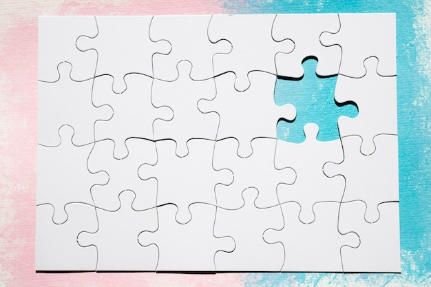 Missing piece of white puzzle over dual colored surface Free Photo