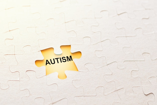 Missing puzzle piece with inscription autism on a yellow background Premium Photo