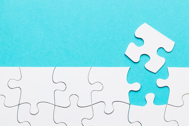 Missing puzzle piece with white puzzle grid on blue background Free Photo