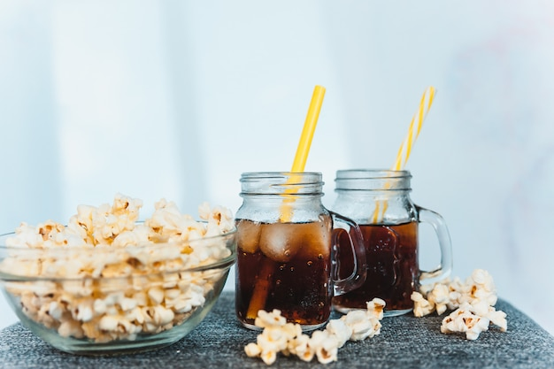 Misted bottles of cola with ice and fresh kettle corn Premium Photo