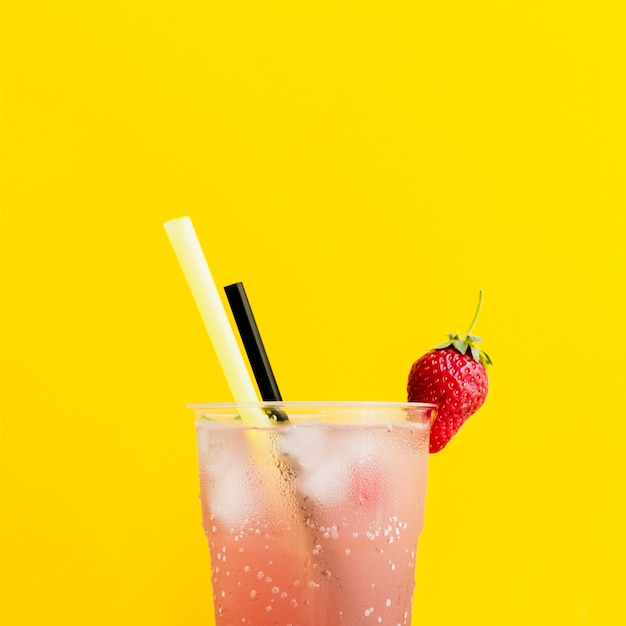 Misted glass of cocktail with strawberry and straws Free Photo