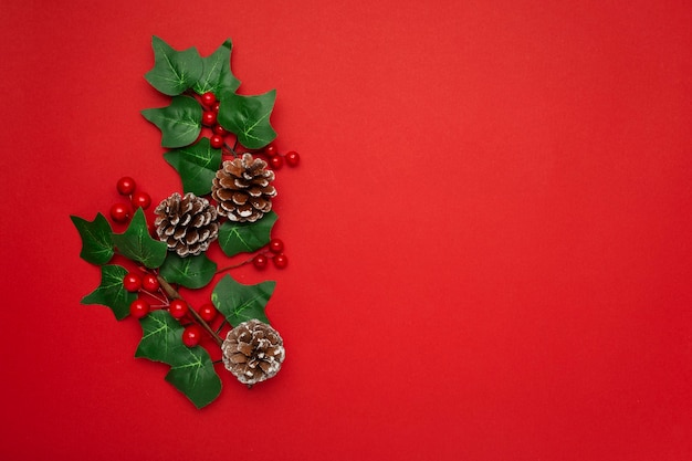 Омела и сосновые шишки на красном столе Бесплатные Фотографии