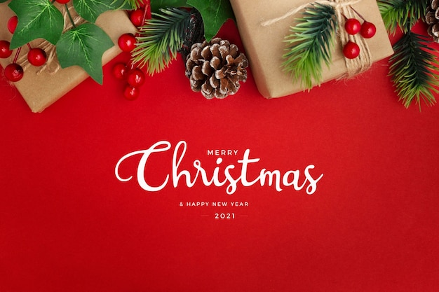 ヤドリギ、松ぼっくり、赤いテーブルの上の贈り物クリスマスの挨拶 無料写真