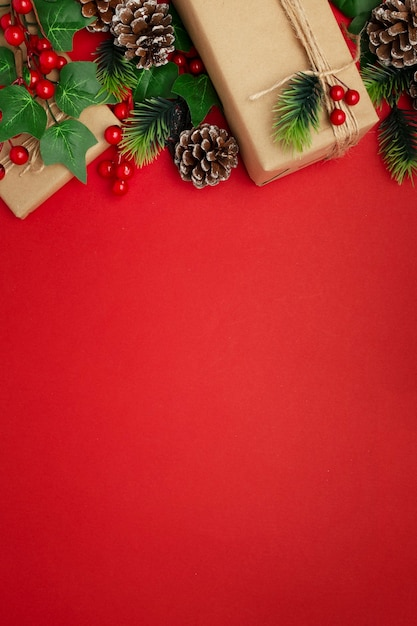 Mistletoe, pine cones and christmas gifts on red table Free Photo