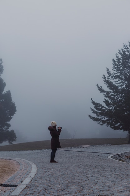 Misty fog landscape in a mountain. young woman taking pictures. winter or autumn concept Premium Photo
