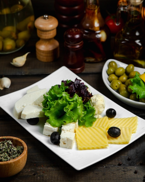 Mix of cheese served with basil and olives Free Photo