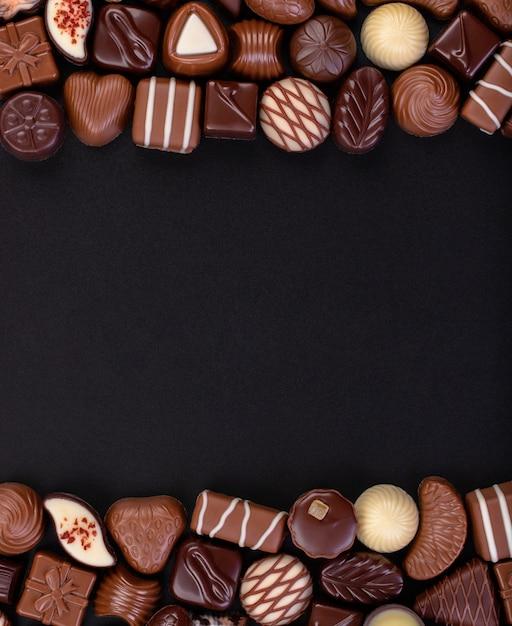 チョコレートのキャンディと黒板背景、甘い食べ物のフレームに他の甘さをミックスします。 Premium写真