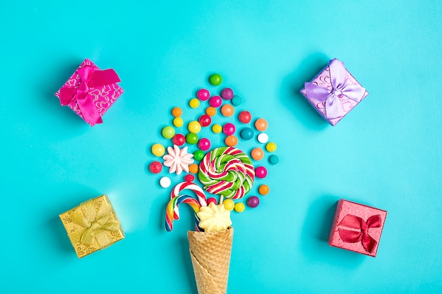 Mix colorful chocolate sweets spilled out of ice cream waffle cone, gift boxes on blue  flat lay Premium Photo