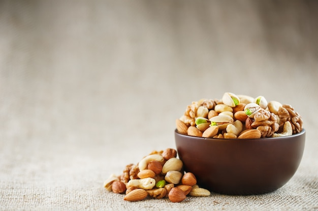 Mix of different nuts in a wooden cup against the background of fabric from burlap Premium Photo