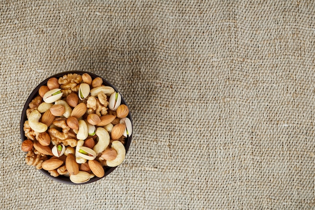 Mix of different nuts in a wooden cup against the  of fabric from burlap. nuts as structure and background, macro. top view. Premium Photo
