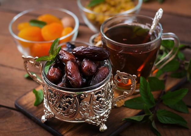 Mix dried fruits (date palm fruits, prunes, dried apricots, raisins) and nuts, and traditional arabic tea. ramadan (ramazan) food. Premium Photo