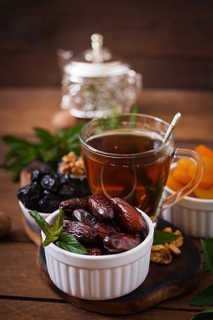 Mix dried fruits (date palm fruits, prunes, dried apricots, raisins) and nuts, and traditional arabic tea. ramadan (ramazan) food. Free Photo
