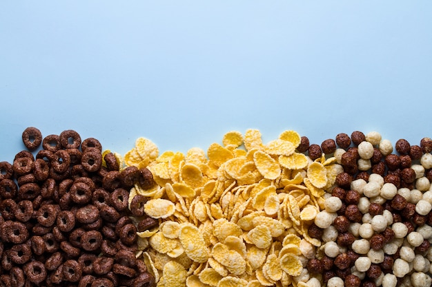 Mix of dry, chocolate balls, rings and yellow corn flakes for cereals breakfast on blue background Premium Photo