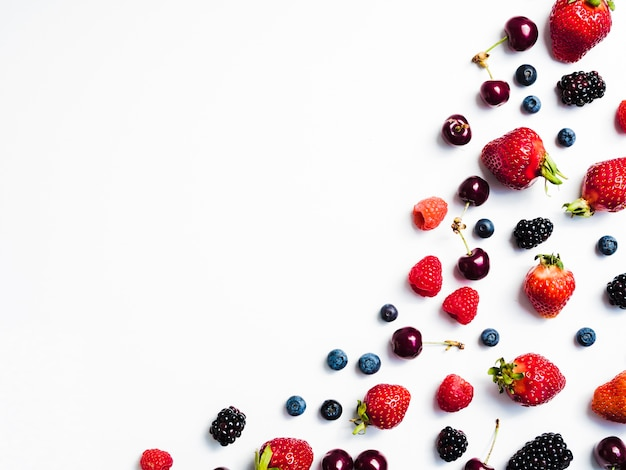 Mix of fresh tasty berries on right of white background Free Photo
